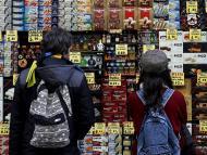 Dos jóvenes miran los precios de un puesto en un mercado de Barcelona