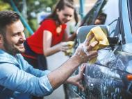 Un hombre limpia su coche