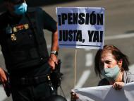 Una mujer con un cartel y una pancarta participa en una manifestación para la mejora del sistema público de pensiones en Madrid