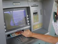 Una mujer saca dinero del cajero
