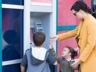 Niños sacando dinero de un cajero automático