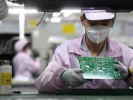 Un trabajador revisa una placa base en una fábrica de Gree en China