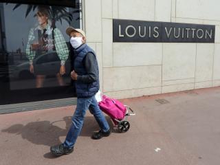Un hombre camina por delante de una tienda de Louis Vuitton en Cannes, Francia
