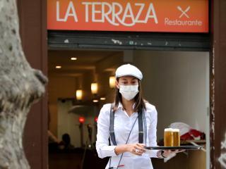 Una camarera con mascarilla sirve 2 cañas en una terraza de Barcelona tras la reapertura de la hostelería