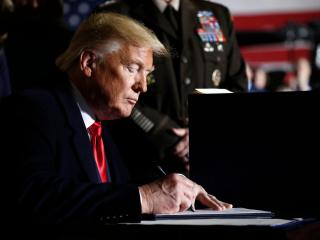 President Donald Trump signs the National Defense Authorization Act for Fiscal Year 2020 at Andrews Air Force Base, Md., Friday, Dec. 20, 2019. Andrew Harnik/AP
