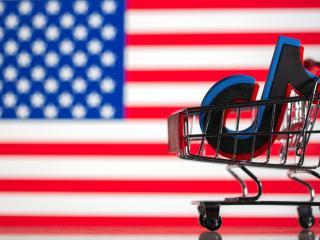Imagen del logotipo de TikTok en un carro de compra sobre la bandera de Estados Unidos.