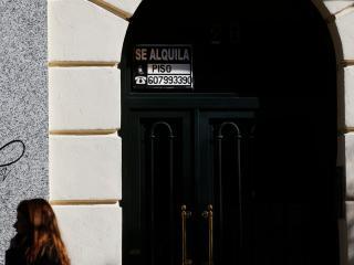 Una joven pasa ante un anuncio de un piso en alquiler en Madrid