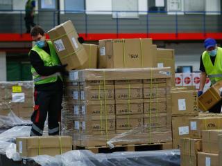 Dos operarios desembalan un palé de paquetes en el aeropuerto de Frankfurt
