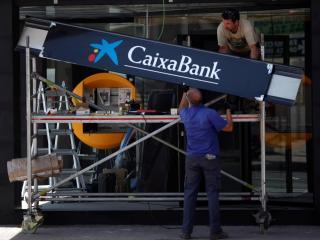 Dos trabajadores colocan el letrero de CaixaBank en una sucursal en Málaga