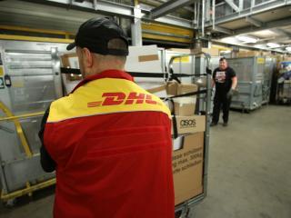 Un operario de DHL mueve un carro con paquetes en un almacén en Alemania