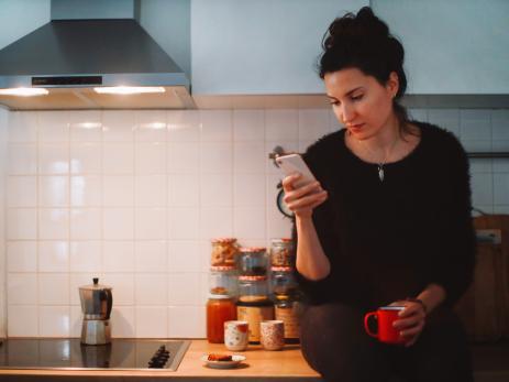Una mujer mira su teléfono móvil en la cocina