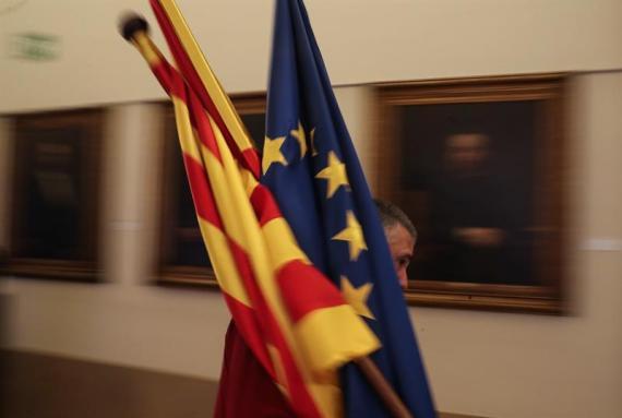 Un trabajador de la sede de la patronal catalana Fomento del Trabajo en Barcelona coloca unas banderas.