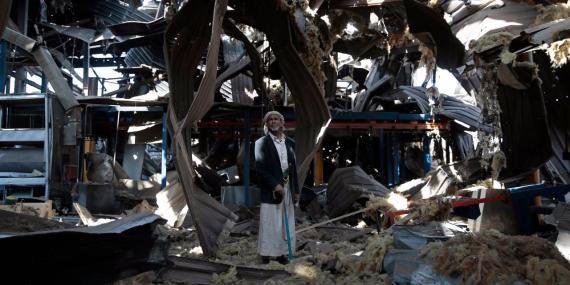 Un hombre mayor se detiene entre las ruinas de una fábrica destrozado por los bombardeos aéreos Sirios en Saná, Yemen, 22 de septiembre de 2016