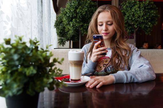 Mirando el móvil en una cafetería