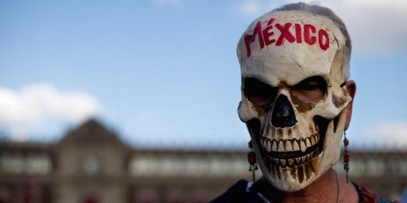 Una mujer enmascarada frente al Palacio Nacional durante un mitin de apoyo a los 43 estudiantes desaparecidos, en el Zócalo, la plaza principal de Ciudad de México, el miércoles 23 de septiembre de 2015.