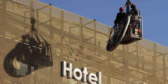 Dos trabajadores desmontan la valla publicitaria de un hotel en Pekín (China) el pasado 30 de noviembre dentro de una operación para embellecer la ciudad.