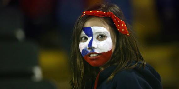 Una niña con la bandera de Chile pintada en su cara durante un partido de la selección nacional de fútbol contra Colombia en el Estadio Monumental de Santiago de Chile el 6 de septiembre de 2016.