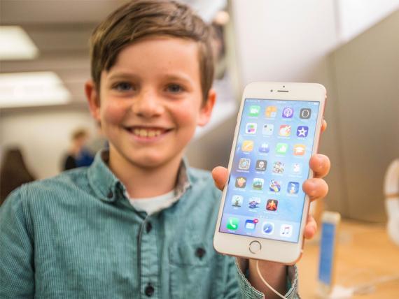Un chico sostiene en la mano un iPhone