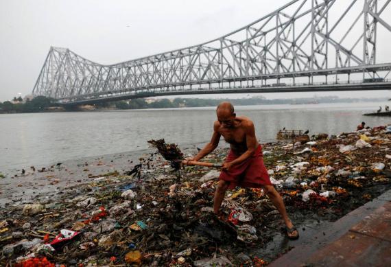 Un hombre recoge basura a lo largo de las orillas del río Ganges en Calcuta (India) el 9 de abril de 2017.