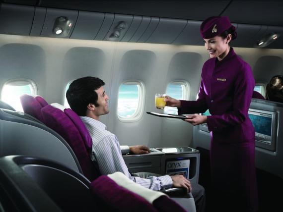 azafata atiende a un pasajero en un vuelo
