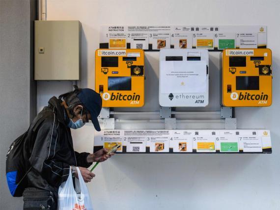 Un hombre utiliza su teléfono mientras pasa junto a un cajero de criptomonedas de Bitcoin y Ethereum en Hong Kong.