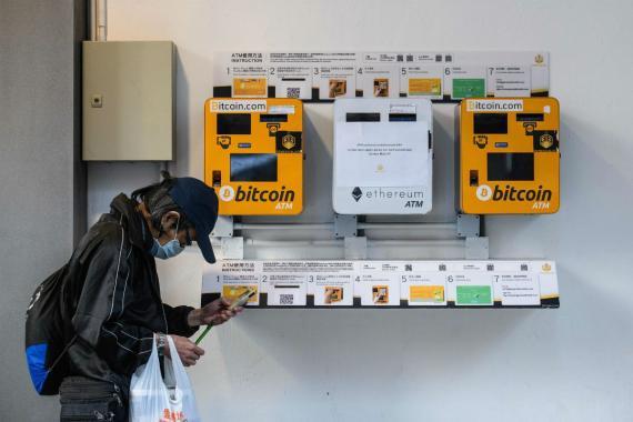 Un hombre utiliza su teléfono mientras pasa por unos cajeros automáticos de bitcoin en Hong Kong (China) el 18 de diciembre de 2017.