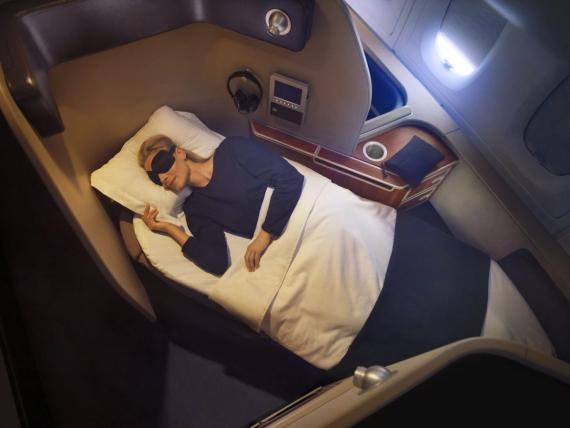 Una pasajera duerme en una cabina de primera clase durante un vuelo.