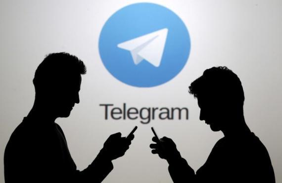Dos hombres posan junto a sus 'smartphone' frente a una pantalla que muestra el logotipo de Telegram.