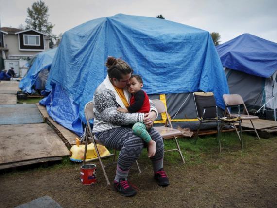 Madre sujeta a su hijo en una zona pobre