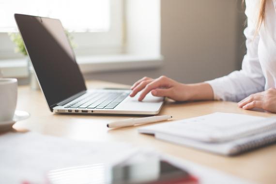 Mujer en un escritorio con cuaderno, boli y portátil