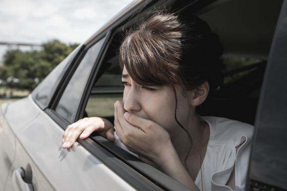 Chica a punto de vomitar en el coche