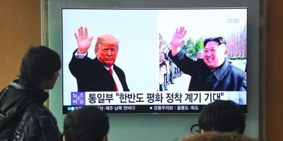 Personas ven las noticias con imágenes del presidente de Estados Unidos, Donald Trump, y del líder norcoreano, Kim Jong Un, en una estación de tren de Seúl