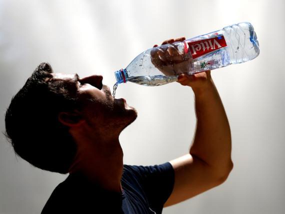 Un hombre bebe agua durante un día caluroso en Bélgica, en julio de 2016