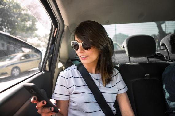 Una joven utiliza un móvil dentro de un coche.