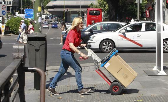 Mujer trabajando llevando un paquete en la calle