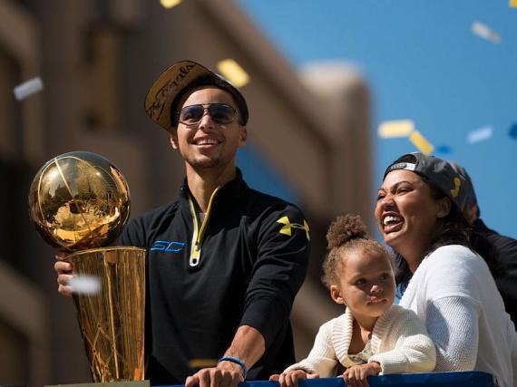 Stephen Curry con su hija Riley y su mujer, Ayesha, durante la cabalgata de celebración de los Golden State Warriors en Oakland (California).