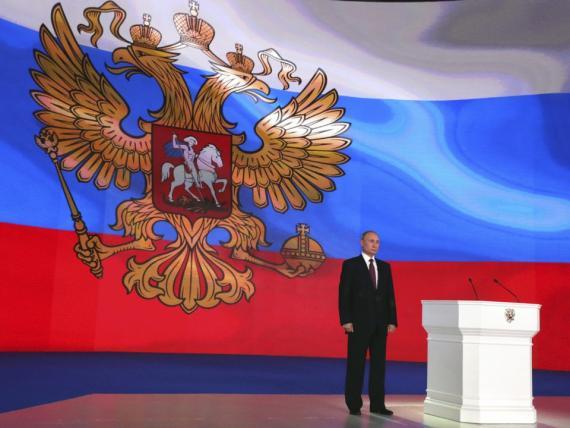Vladimir Putin de pie delante de una bandera nacional