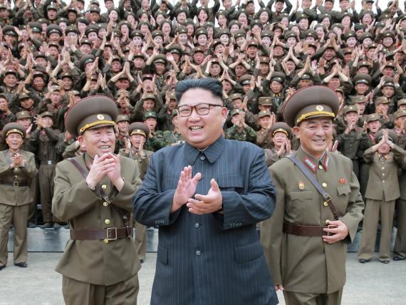 El líder norcoreano Kim Jong Un aplaude con oficiales militares en el Comando de la Fuerza Estratégica del Ejército Popular de Corea.