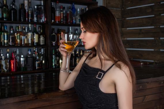 Una mujer toma una bebida alcohólica