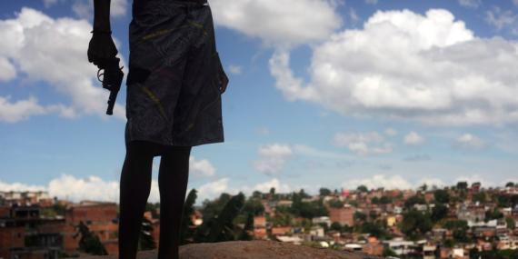 Un narcotraficante brasileño apodado Giant, de 17 años, posa con una pistola sobre una colina que domina un barrio marginal en Salvador, estado de Bahía, el 11 de abril de 2013.
