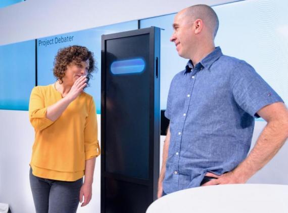 La Dr. Ranit Aharonov (izquierda) susurrando a Project Debater, un sistema de Inteligencia Artificial de IBM que es capaz de debatir sobre humanos. Ella y el Dr. Noam Slonim son dos de los científicos involucrados en el desarrollo de Project Debater.