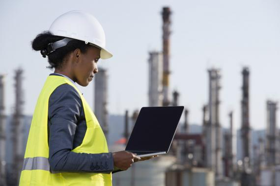Una ingeniera en una refinería trabajando con su ordenador.