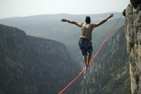 Un hombre haciendo equilibrios sobre una cuerda.
