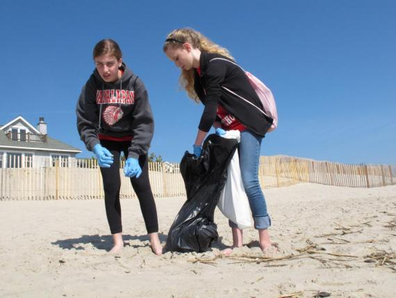 In an April 21, 2012 photo, Melissa Shapero reacts with disgust after picking up a cigarette butt from the beach in Point Pleasant Beach N.J. as Sarah Steward holds a trash bag for her.