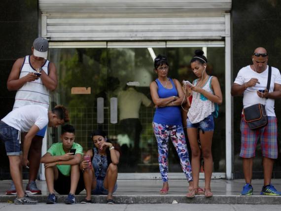 Cubanos conectándose a internet mediante Wi-Fi pública.