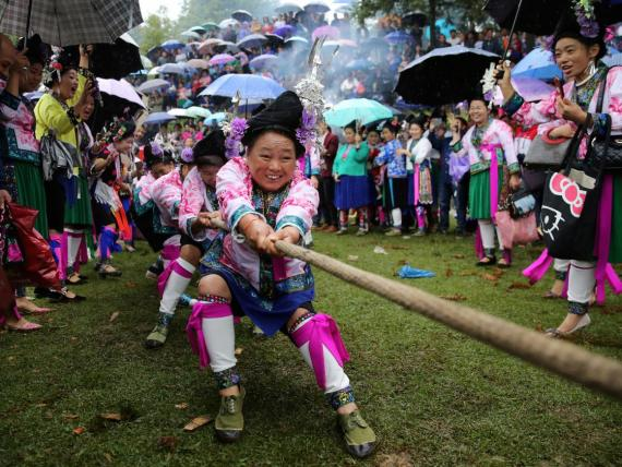 Las mujeres de etnia miao con trajes tradicionales participan en un tira y afloja para celebrar un festival local en una aldea en el condado autónomo Miao de Rongshui, región autónoma de Guangxi Zhuang, China.