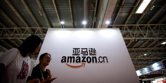 Los visitantes pasan junto a un logotipo de Amazon China en la Feria Internacional del Libro de Beijing en Beijing el 23 de agosto de 2017.