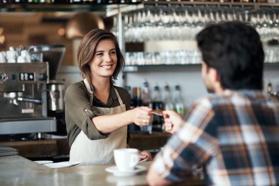 Un cliente paga con tarjeta en una cafetería.