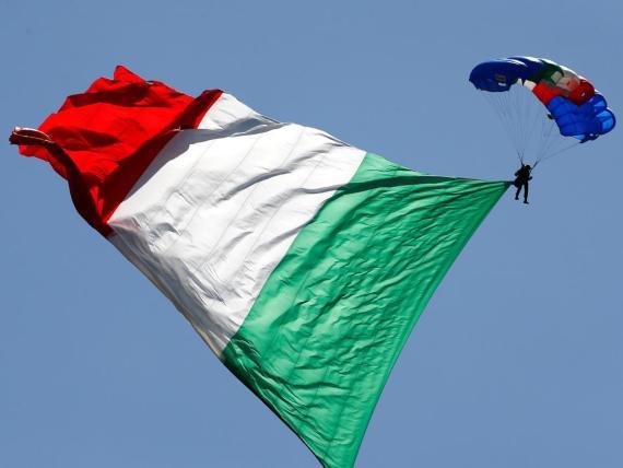 Un paracaidista del ejército italiano izando la bandera italiana durante el desfile militar del Día de la República en Roma.