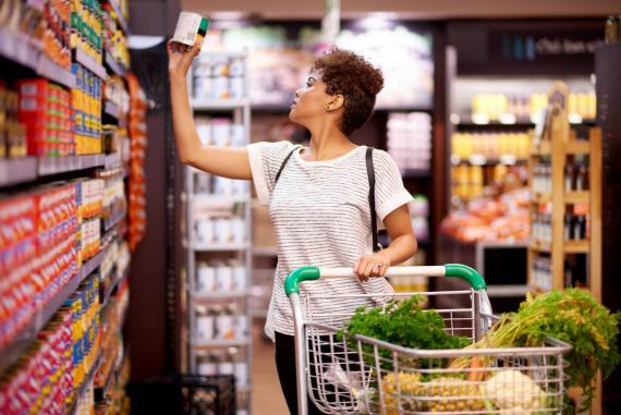 Una mujer mira un envase en un supermercado.